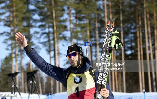 Fifth placed Martin Fourcade of France greets spectators after the men's 125 km pursuit at the IBU Biathlon World Cup in Kontiolahti Finland on March...