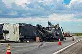 Fifth wheel Recreational Vehicle overturned on a highway with the underside torn up and things spilling out into the roadway after an accident