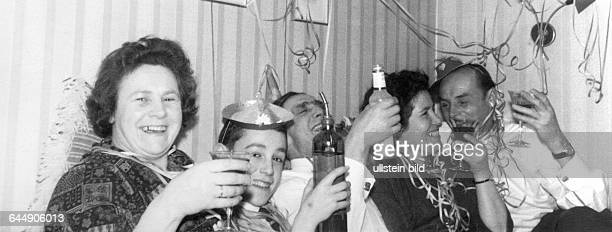 Fifties family celebration celebrating New Years living room paper streamers alcoholic drinks emotion cheerfulness fun laughter women 40 to 50 years...