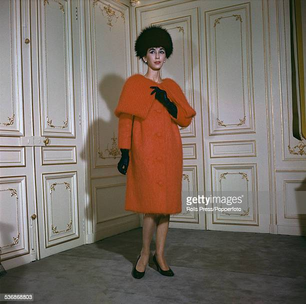 Fifties Fashion A female model wears a soft mohair wool outfit in vivid orange with a cape collar of mushroom ribbing and a black velvet busby and...
