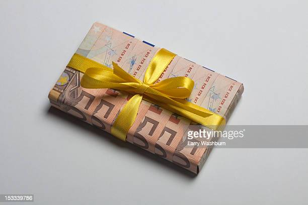 Fifty Euro banknotes used to wrap a gift with a yellow bow