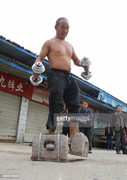 Fiftyfiveyearold man Huang Baoquan walks with two stones which weigh about 53 kilograms on the street of Qingyang District on October 29 2015 in...