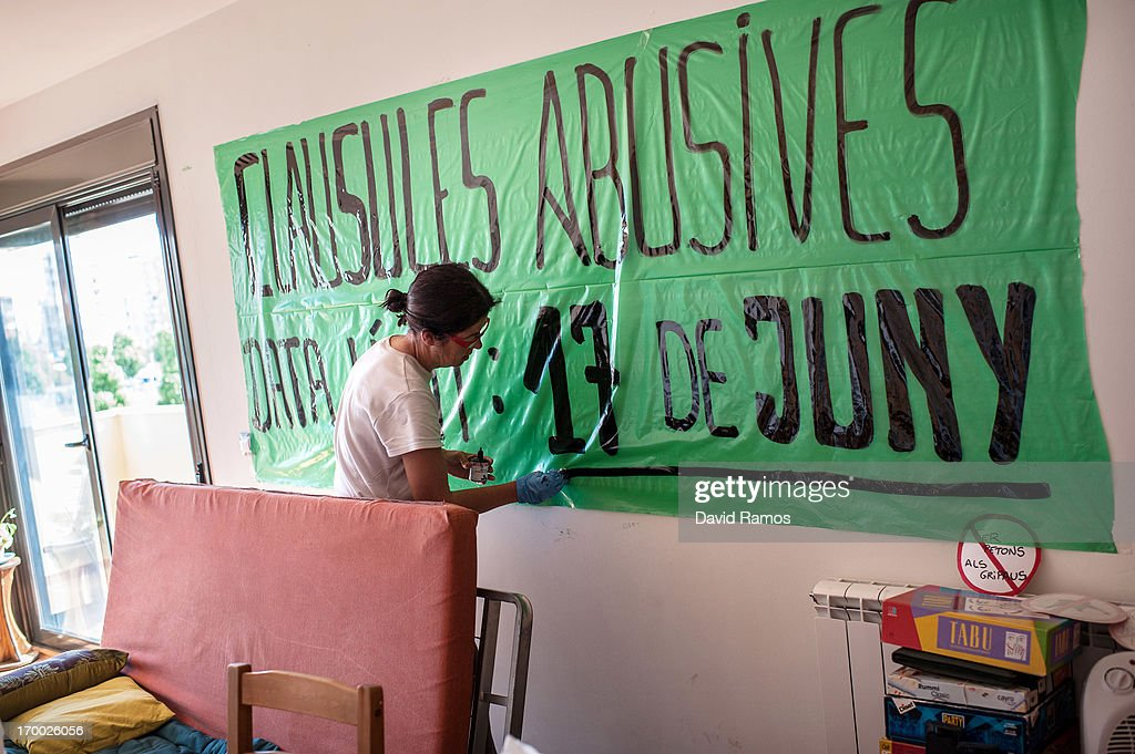 Fifty-three year old Engracia Caselles, a teacher unemployed for one year, paints a banner in her shared apartment of an occupied newly constructed building where she moved with her twenty-three years old daughter two months ago after being unable to afford to pay rent, on June 5, 2013 in Salt, Spain. In 2010 Spanish banks foreclosed on more than 100,000 households contributing to the already large number of empty houses in Spain. With as many as one million properties unsold victims of Spain's financial crisis have turned to squatting in the empty buildings. This building has stood empty for two years before the anti-eviction platform of Girona and several homeless families moved in three months ago. The community houses a total of 8 families who have to suffer water and electricity cuts and live with the fear of eviction.