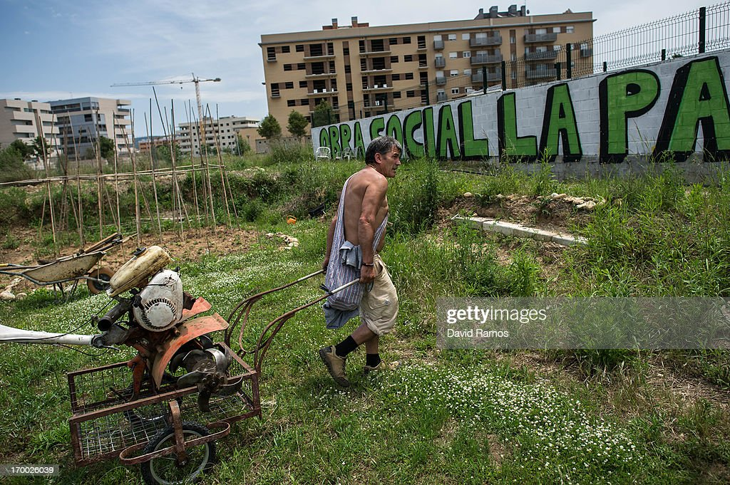 Fifty-three year old Joan, unemployed for three years, carries a cultivator on a plot next to an occupied newly constructed building where he moved two months ago due to being unable to afford to pay rent, on June 5, 2013 in Salt, Spain.In 2010 Spanish banks foreclosed on more than 100,000 households contributing to the already large number of empty houses in Spain. With as many as one million properties unsold victims of Spain's financial crisis have turned to squatting in the empty buildings. This building has stood empty for two years before the anti-eviction platform of Girona and several homeless families moved in three months ago. The community houses a total of 8 families who have to suffer water and electricity cuts and live with the fear of eviction.