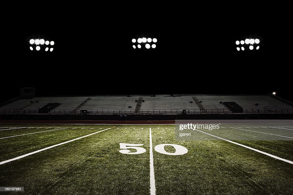 Fifty-yard line of football field at night : Stock Photo