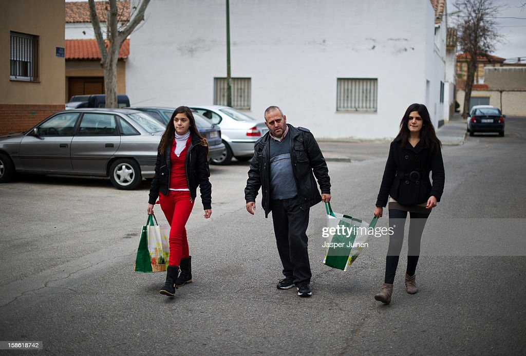 Fifty-year old unemployed former door factory worker Luis Gonzales (C), who has been without welfare payment now for two months being unable to pay his 160 Euro (211 US Dollars) a month morgage, his electicity and heating bills, walks home with his daughters, nineteen year old Maria (R) and fifteen year old Jennifer, carrying a food hand received at a Red Cross point on December 21, 2012 in Villacanas, Spain. During the boom years, where in its peak Spain built some 800,000 houses a year accompanied by the manufacturing of millions of wooden doors, the people of Villacanas were part of Spain's middle class enjoying high wages and permanent jobs. During these construction boom years the majority of the doors used within these new developments were made in this small industrial town. Approximately seven million doors a year were once assembled here and the factories employed a workforce of almost 5700 people. The town is now left almost desolate with the Villacanas industrial park empty and redundant. With Spain in the grip of recession and the housing bubble burst, Villacanas is typical of many former buoyant industrial Spanish towns now struggling with huge unemployment problems.