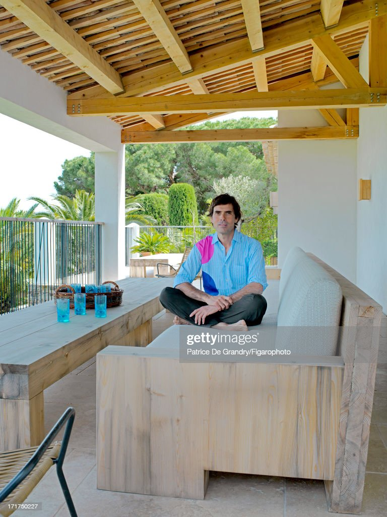 104642-003. Architect Pierre Yovanovitch is photographed for Madame Figaro on May 1, 2013 in St Tropez, France. Yovanovitch sits on a solid pine sofa that he designed himself. PUBLISHED IMAGE.