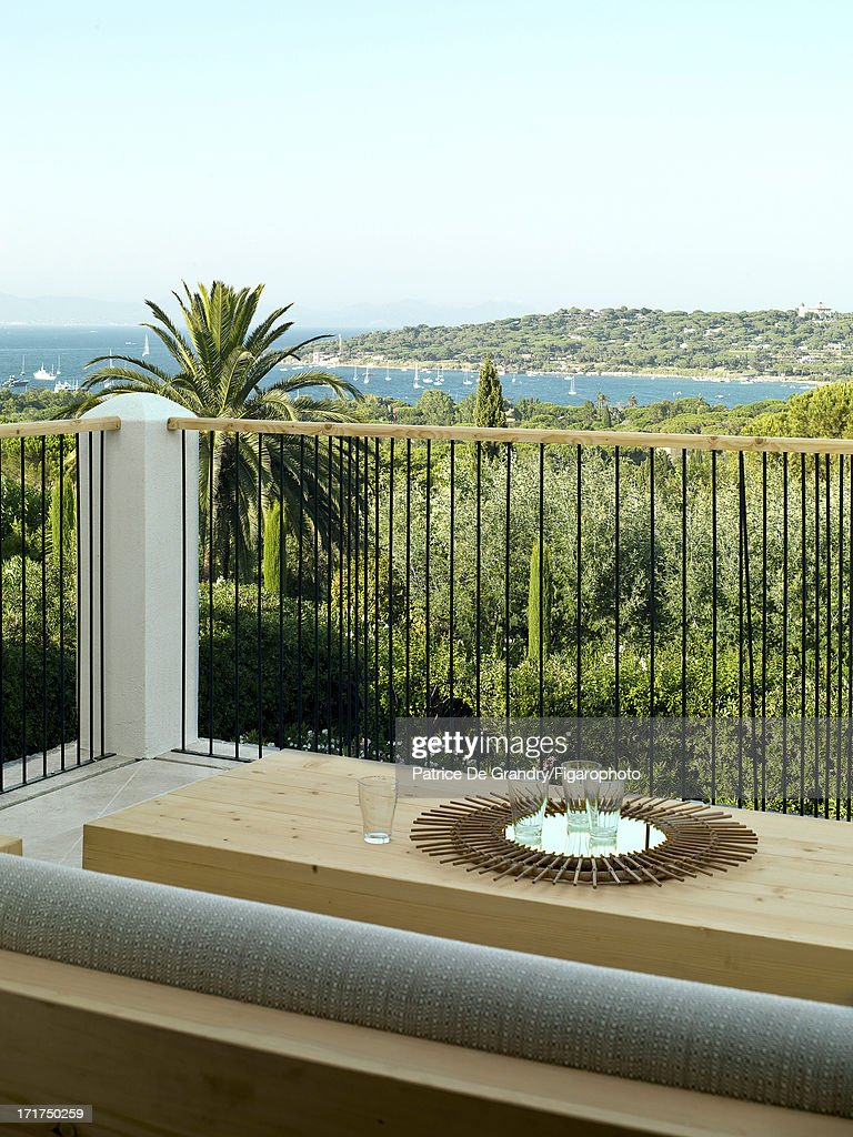 104642-006. A holiday home designed by architect Pierre Yovanovitch is photographed for Madame Figaro on May 1, 2013 in St Tropez, France. Terrace overlooking Canebiers Bay. Solid pine outdoor sofa designed by the architect. PUBLISHED IMAGE.
