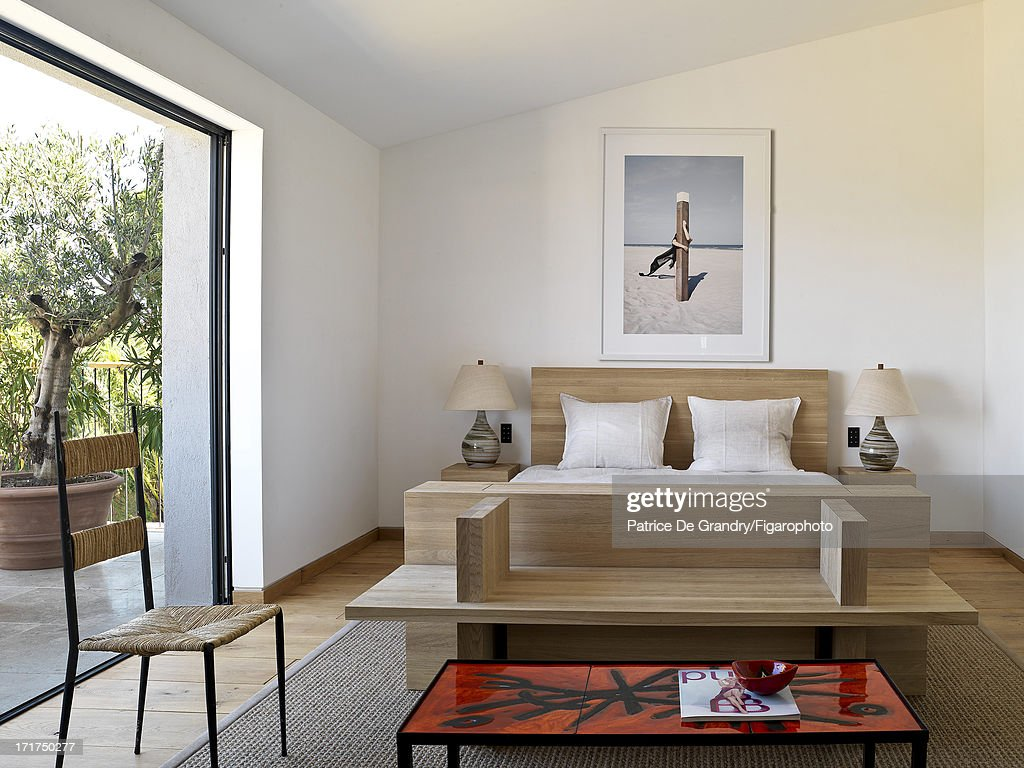 104642-009. A holiday home designed by architect Pierre Yovanovitch is photographed for Madame Figaro on May 1, 2013 in St Tropez, France. A solid pine bed and a Roger Capron table. Wall photo by Arnaud Lajeunie, Anne de Villepoix Gallery. PUBLISHED IMAGE.