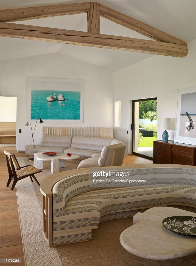104642-010. A holiday home designed by architect Pierre Yovanovitch is photographed for Madame Figaro on May 1, 2013 in St Tropez, France. The living room is articulated around two sinuous linen-covered sofas. 1950s stylings with two Harvey Pobber low tables in travertine, ceramics by Jean Lurçat, a Paul Laszlo chair and a Robsjohn Gibbings commode. Wall photo by Massimo Vitali. PUBLISHED IMAGE.
