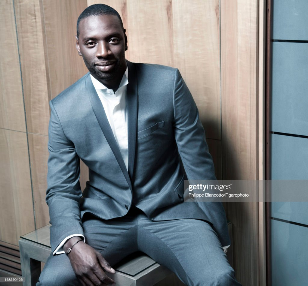 105646-003. Actor Omar Sy is photographed for Madame Figaro on December 10, 2012 in Paris, France. PUBLISHED IMAGE. Jacket, pants, shirt (Dior Homme), bracelet (Hermes).