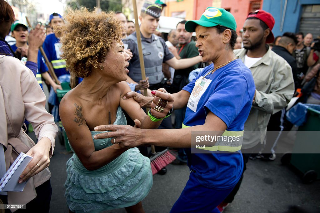 A fight breaks out between a crack addict and a street cleaner as Prince Harry leaves after his visit to 'Cracolandia', an extremely deprived area of Sao Paulo with a high concentration of crack addicts on June 26, 2014 in Sao Paulo Brazil. Crack in Sao Paulo costs just 80 UK pence for a rock of the drug. Prince Harry is on a four day tour of Brazil that will be followed by two days in Chile.