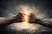 Fight, close up of two fists hitting each other over dramatic sky