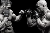 Two muscular guys fighting in front of black background