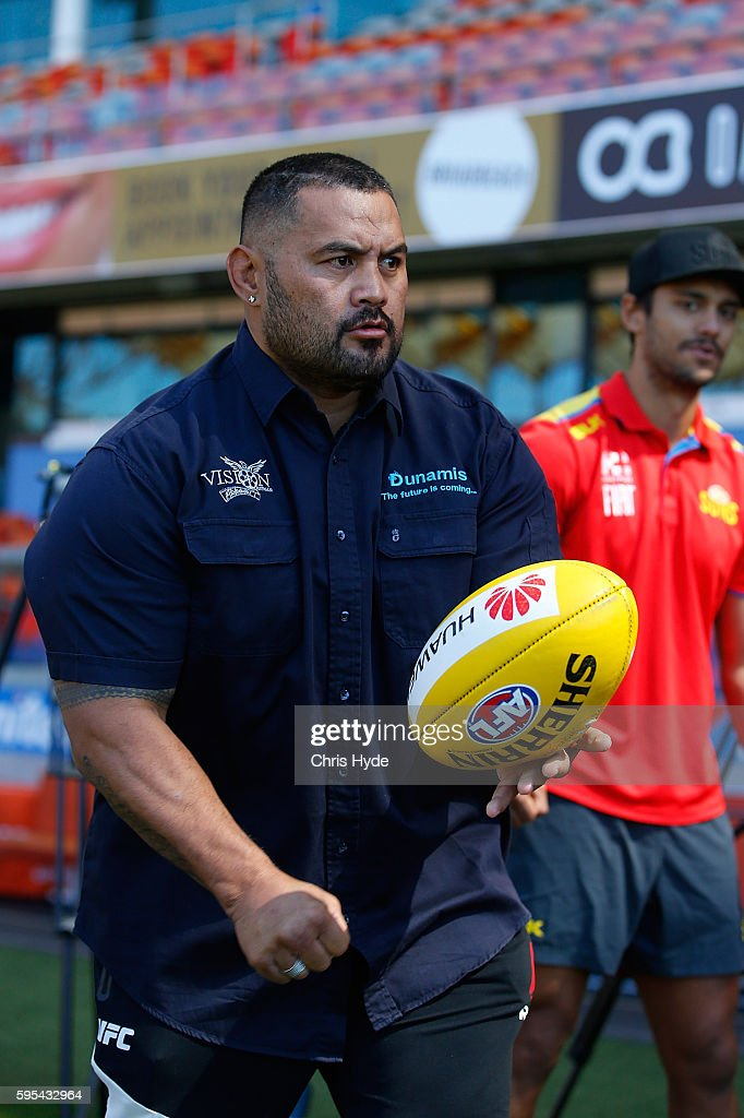 UFC fighter and Dunamis actor Mark Hunt handballs with Aaron Hall of the AFL Gold Coast Suns at Metricon Stadium on August 26 2016 in Gold Coast...