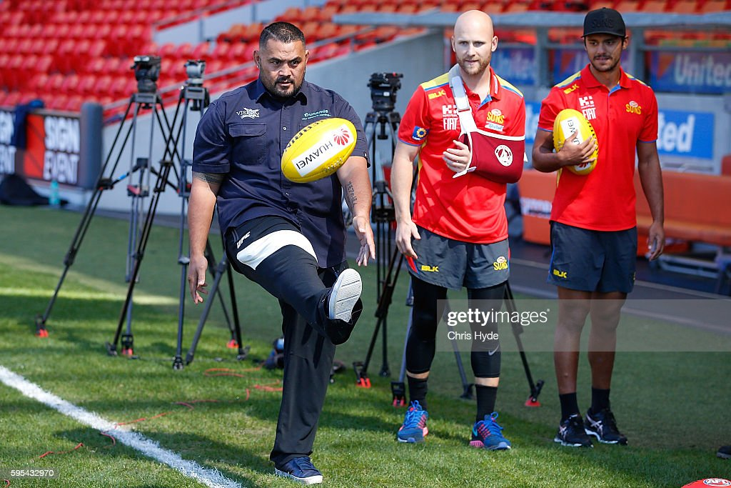 UFC fighter and Dunamis actor Mark Hunt kicks with Gary Ablett and Aaron Hall of the AFL Gold Coast Suns at Metricon Stadium on August 26 2016 in...