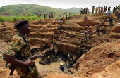 fighter controls workers at the gold mine in Iga Barriere 18 June 2003 Ituri region northeast of Democratic Republic of Congo The region' s huge gold...
