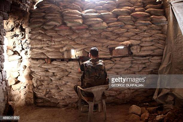 A fighter from a local popular committee which supports the Syrian government forces guards a look out point in the Hamidiyeh neighbourhood of the...