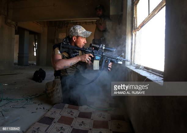 TOPSHOT A fighter from Iraq's elite CounterTerrorism Service takes cover inside a building in the Shuhada neighbourhood of west Mosul on March 10...