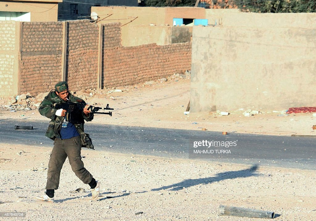 A fighter from the Fajr Libya coalition of militias who seized Tripoli at the end of August driving out national rival militiamen runs during clashes...