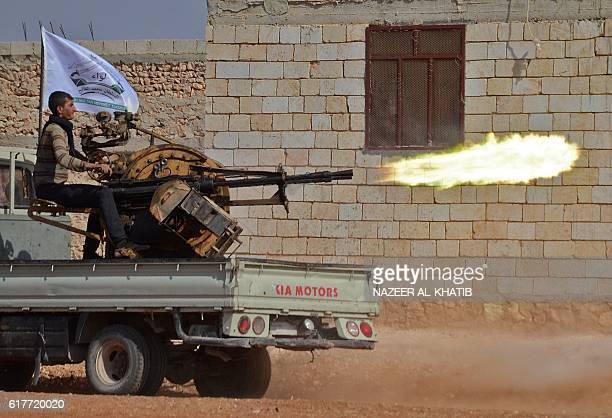 A fighter from the Free Syrian Army fires an antiaircraft machine gun mounted on a vehicle deployed during fighting against Islamic State group...