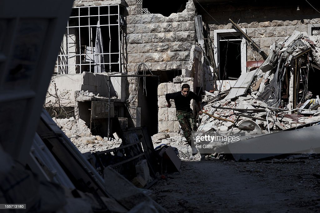 A fighter from the Free Syrian Army leaps across debris left in the street while running across a 'sniper alley' near the Salahudeen district on November 4, 2012 in Aleppo, Syria. The Shohada al Haq, or 'Martyrs of Truth' brigade control an area on the edge of the Salahudeen district in Aleppo, Syria's largest city. The brigade is made up of around 70 men, holding a handful of positions hidden in apartment blocks on the front line of Aleppo, facing toward Syrian army positions sometimes less than one hundred meters away. The Shohada al Haq use snipers to target Syrian regime troops as they move on the other side of the front, as well as moving between apartment blocks in the 'no man's land' between the two forces, occupying positions of advantage over the Syrian military. The brigade, or 'Katiba', live in the apartments they occupy, and the unit of rebel fighters is made up of former soldiers who defected from the Syrian military alongside men from Aleppo and other cities across Syria who have chosen to fight in Syria's increasingly violent civil war. (Photo by Ed Giles/Getty Images).