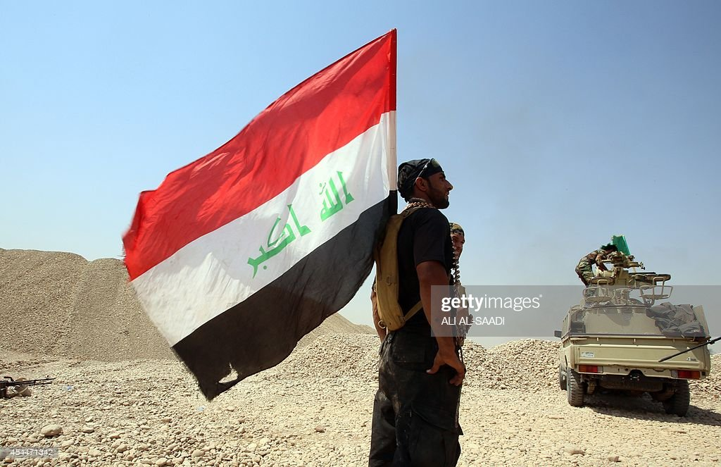 A fighter from the Iraqi Imam Ali Brigade stands with the Iraqi flag flaying from his backpack during heavy clashes with Islamic State militants in...