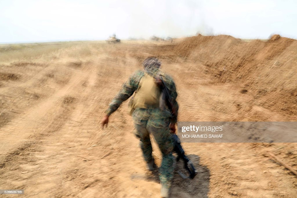 A fighter from the Iraqi pro-government forces advances during an operation to retake the town of al-Bashir, near Kirkuk, from the Islamic State group (IS), on April 30, 2016. Iraqi forces launched a final assault Saturday to retake the Turkmen majority town of Bashir from the Islamic State jihadist group, Kurdish authorities said. 'Bashir village is surrounded and 80 percent has been cleared,' the Kurdistan Region Security Council said on social media. Turkmen units from Iraq's Hashed al-Shaabi (Popular Mobilisation) militia umbrella group, which announced an operation to retake the town earlier this month, were also taking part. / AFP / Mohammed SAWAF