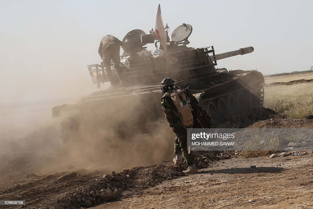 A fighter from the Iraqi pro-government forces mans a tank during an operation to retake the town of al-Bashir, near Kirkuk, from the Islamic State group (IS), on April 30, 2016. Iraqi forces launched a final assault Saturday to retake the Turkmen majority town of Bashir from the Islamic State jihadist group, Kurdish authorities said. 'Bashir village is surrounded and 80 percent has been cleared,' the Kurdistan Region Security Council said on social media. Turkmen units from Iraq's Hashed al-Shaabi (Popular Mobilisation) militia umbrella group, which announced an operation to retake the town earlier this month, were also taking part. / AFP / Mohammed SAWAF