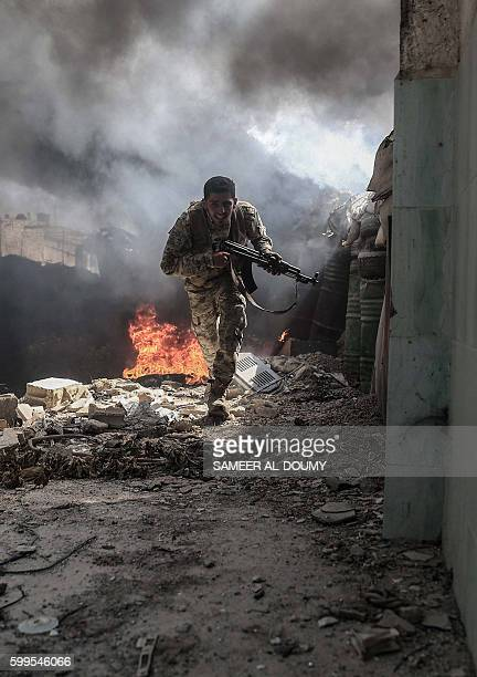 TOPSHOT A fighter from the Jaish alIslam runs to avoid sniper fire in the village of Tal alSiwan area of the rebelheld stronghold of Douma on the...