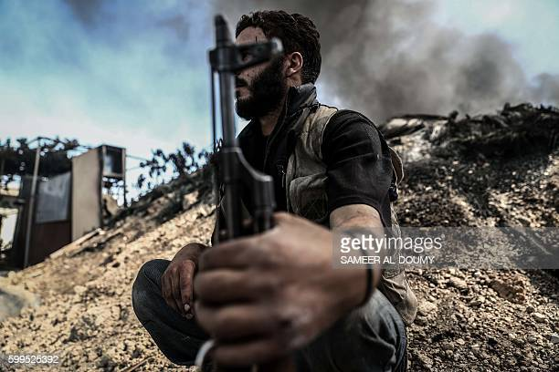 TOPSHOT A fighter from the Jaish alIslam sits near smoke billowing on the frontline which they use to take cover in the village of Tal alSiwan area...