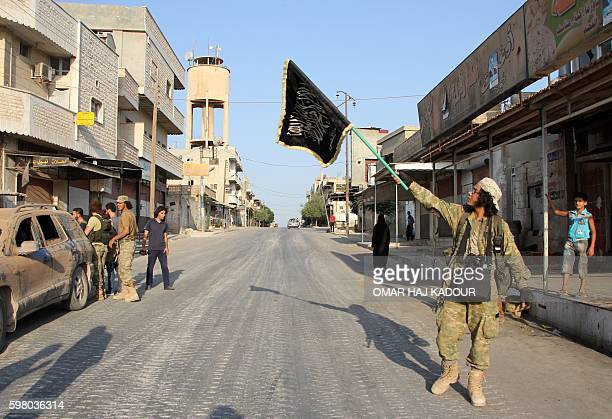 A fighter from the Jund alAqsa Islamist Brigade raises an Islamist flag after taking control of the northern Syrian town of Tayyibat alImam northwest...