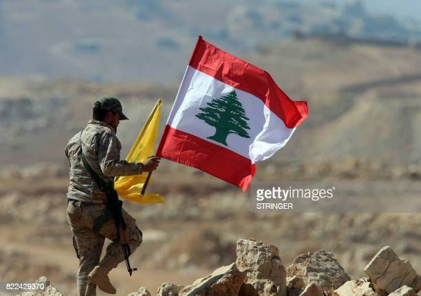 A fighter from the Lebanese Shiite Hezbollah movement holds the Lebanese and the party's flag during a press tour in a mountainous area around the...