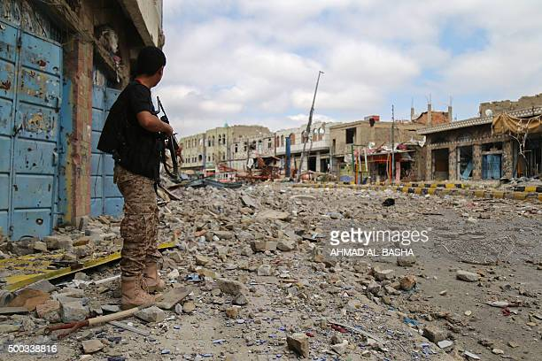 A fighter from the Popular Resistance Committees loyal to Yemen's President Abedrabbo Mansour Hadi stands in a heavily damaged street in the...