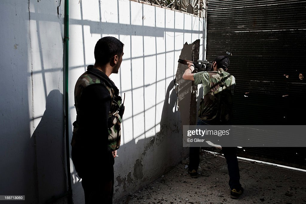 A fighter from the Shohada al Haq brigade of the Free Syrian Army aims a sniper rifle through a newly created 'mousehole' during a raid to clear a new apartment building in the no-mans land area near the Salahudeen district on November 3, 2012 Aleppo, Syria. The Shohada al Haq, or 'Martyrs of Truth' brigade control an area on the edge of the Salahudeen district in Aleppo, Syria's largest city. The brigade is made up of around 70 men, holding a handful of positions hidden in apartment blocks on the front line of Aleppo, facing toward Syrian army positions sometimes less than one hundred meters away. The Shohada al Haq use snipers to target Syrian regime troops as they move on the other side of the front, as well as moving between apartment blocks in the 'no man's land' between the two forces, occupying positions of advantage over the Syrian military. The brigade, or 'Katiba', live in the apartments they occupy, and the unit of rebel fighters is made up of former soldiers who defected from the Syrian military alongside men from Aleppo and other cities across Syria who have chosen to fight in Syria's increasingly violent civil war. (Photo by Ed Giles/Getty Images).