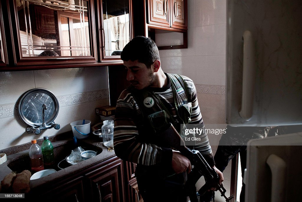 A fighter from the Shohada al Haq brigade of the Free Syrian Army moves through an abandoned kitchen during a raid to clear a new apartment building in the no-mans land area near the Salahudeen district on November 3, 2012 in Aleppo, Syria. The Shohada al Haq, or 'Martyrs of Truth' brigade control an area on the edge of the Salahudeen district in Aleppo, Syria's largest city. The brigade is made up of around 70 men, holding a handful of positions hidden in apartment blocks on the front line of Aleppo, facing toward Syrian army positions sometimes less than one hundred meters away. The Shohada al Haq use snipers to target Syrian regime troops as they move on the other side of the front, as well as moving between apartment blocks in the 'no man's land' between the two forces, occupying positions of advantage over the Syrian military. The brigade, or 'Katiba', live in the apartments they occupy, and the unit of rebel fighters is made up of former soldiers who defected from the Syrian military alongside men from Aleppo and other cities across Syria who have chosen to fight in Syria's increasingly violent civil war. (Photo by Ed Giles/Getty Images).