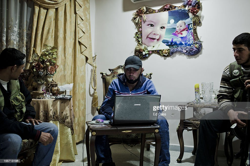 A fighter from the Shohada al Haq brigade of the Free Syrian Army works on a laptop computer in an occupied apartment near the Salahudeen district on November 2, 2012 in Aleppo, Syria. The Shohada al Haq, or 'Martyrs of Truth' brigade control an area on the edge of the Salahudeen district in Aleppo, Syria's largest city. The brigade is made up of around 70 men, holding a handful of positions hidden in apartment blocks on the front line of Aleppo, facing toward Syrian army positions sometimes less than one hundred meters away. The Shohada al Haq use snipers to target Syrian regime troops as they move on the other side of the front, as well as moving between apartment blocks in the 'no man's land' between the two forces, occupying positions of advantage over the Syrian military. The brigade, or 'Katiba', live in the apartments they occupy, and the unit of rebel fighters is made up of former soldiers who defected from the Syrian military alongside men from Aleppo and other cities across Syria who have chosen to fight in Syria's increasingly violent civil war. (Photo by Ed Giles/Getty Images).