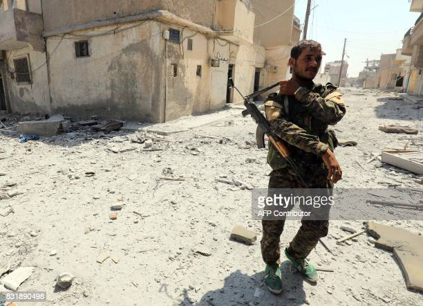 A fighter from the Syrian Democratic Forces a US backed KurdishArab alliance walks in an eastern area of the embattled northern Syrian city of Raqa...