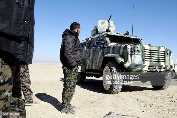 A fighter from the Syrian Democratic Forces inspects a military vehicle supplied by the USled coalition as they gather near a village northeast of...