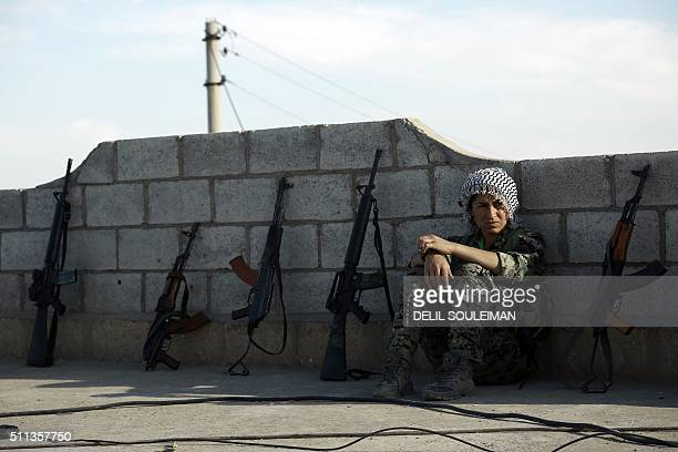 TOPSHOT A fighter from the Syrian Democratic Forces rests on a rooftop on the outskirts of the town of alShadadi in the northeastern Syrian province...