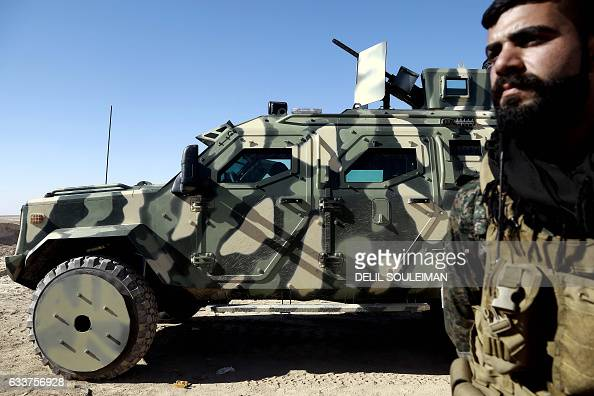 A fighter from the Syrian Democratic Forces stands next to a military vehicle supplied by the USled coalition as they gather near a village northeast...