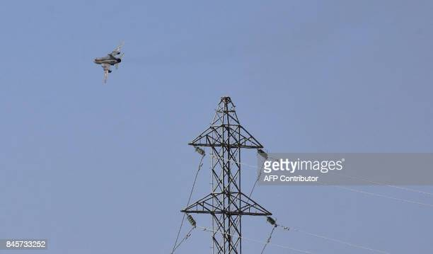 A fighter jet flies over the eastern Syrian city of Deir Ezzor on September 11 2017 as Syrian government forces continue to press forward with...