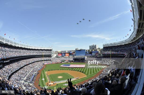 Fighter jets fly overhead during the national anthem as the teams line the basepaths and a giant American flag is held aloft in centerfield prior to...