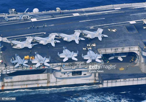 Fighter jets line up on the deck of the aircraft carrier USS Carl Vinson off Tsushima Island in Japan's Nagasaki Prefecture in this photo taken from...