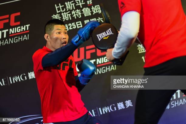 MMA fighter Li Jingliang of China fights with a trainer during an open workout session prior to UFC Fight Night in Shanghai on November 23 2017 / AFP...