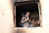 TOPSHOT A fighter loyal to Libya's internationally recognised government checks a damaged house in Benghazi after they seized the centre of the...