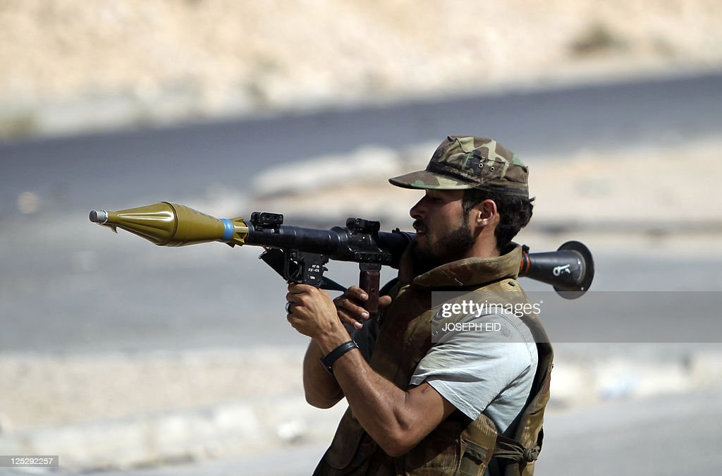 A fighter loyal to Libya's new leaders readies to fire his Rocket Propelled Grenade during clashes with proKadhafi armed men inside the city of Bani...