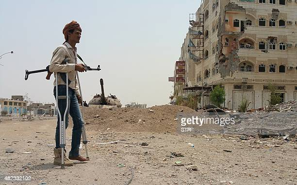 A fighter loyal to Yemen's exiled President Abedrabbo Mansour Hadi walks with crutches in Yemen's second city of Aden on July 30 2015 Rebel forces in...