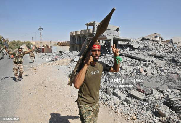 TOPSHOT A fighter of the Hashed AlShaabi flashes the victory gesture while carrying a rocketpropelled grenade launcher during the advance through the...