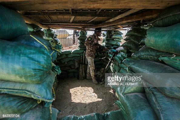 TOPSHOT A fighter of the Hashed alShaabi paramilitaries stands guard in a foxhole near the frontline village of Shar'iah on the outskirts of Tal Afar...